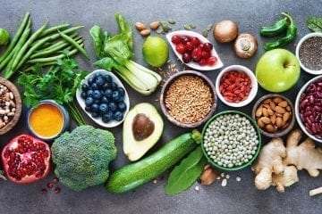 What is Whole Food Plant-Based Diet? Healthy food selection with fruits, vegetables, seeds, superfood, cereals on grey background.